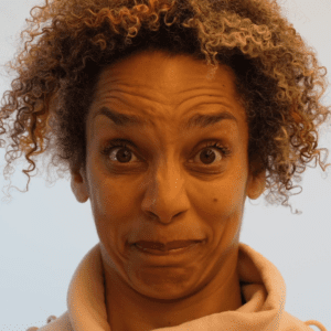 Alice Sheppard, a light skinned multiracial Black woman with brown eyes and blonde, mustard, and brown striped curly hair, wears a peach colored sweatshirt. In this video, she performs a face dance moving in and out of a series of intense facial expressions to create a dance capturing some of the feelings of forgetting. In between some of these expressions, an AI intervenes. Time slows as we watch the AI create the transition, by changing Alice's facial features and interpreting her face through its own lens. In this still her eyebrows are lifted and she looks both uncomfortable and surprised.