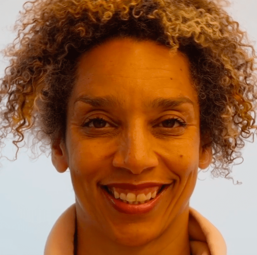 Alice Sheppard, a light skinned multiracial Black woman with brown eyes and blonde, mustard, and brown striped curly hair, wears a peach colored sweatshirt. In this video, she performs a face dance moving in and out of a series of intense facial expressions to create a dance capturing some of the feelings of forgetting. In between some of these expressions, an AI intervenes. Time slows as we watch the AI create the transition, by changing Alice's facial features and interpreting her face through its own lens. In this still, she smiles.