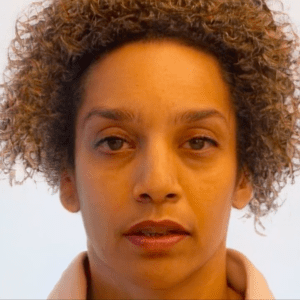 Alice Sheppard, a light skinned multiracial Black woman with brown eyes and blonde, mustard, and brown striped curly hair, wears a peach colored sweatshirt. In this video, she performs a face dance moving in and out of a series of intense facial expressions to create a dance capturing some of the feelings of forgetting. In between some of these expressions, an AI intervenes. Time slows as we watch the AI create the transition, by changing Alice's facial features and interpreting her face through its own lens. AI has smoothed her skin and blurred her eyes. Her both is slightly open. Neutral expression.
