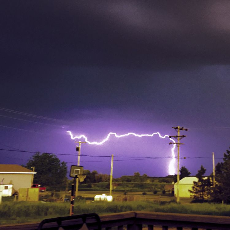 bolt of lightning against telephone poles with a purple sky