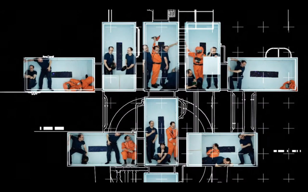 Men in orange and black outfits in several boxes on the screen, on a black designed background