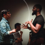 Two artists chatting and using their hands to communicate in a dark room with another artist in the background