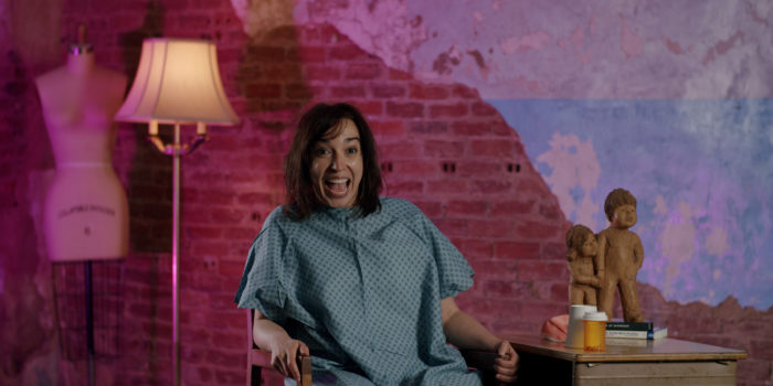 a woman in a hospital gown sits in front of a pink brick wall