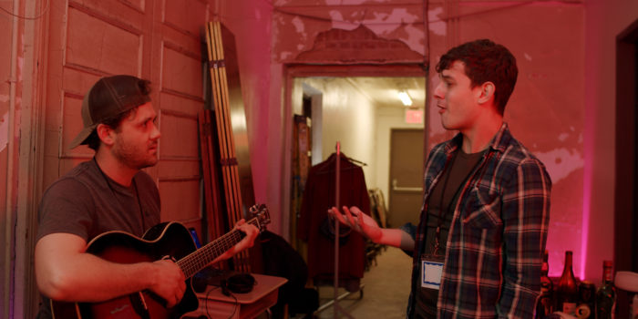 two men speak in a backstage hallway, one holds a guitar
